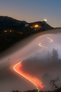 Full moonrise over foggy Malibu with car trails