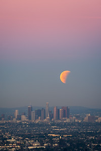 Partial lunar eclipse setting behind Los Angeles with alpenglow