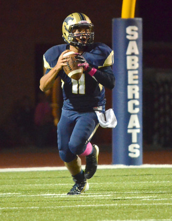 Southmoore quarterback Tre Edwards (11) looks for an open receiver to pass the ball to during the Sabercats' game against Norman High Friday night at Moore Stadium.<br /> Kyle Phillips/The Transcript