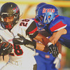 Westmoore's Lexus Leem (28) pushes away a Moore defender as he runs with the ball Friday during the Moore War football game at Moore Stadium.<br /> Kyle Phillips/The Transcript