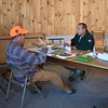 John Holyoke of the BDN (left) discusses some of the details of his 2017 hunt with Maine Department of Inland Fisheries and Wildlife biologist Scott McLellan at the Greenville tagging station after harvesting a bull moose in Somerset County. (Pete Warner | BDN)