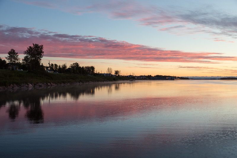 Moose River shoreline in Moosonee looking down river. Purple clouds and water.