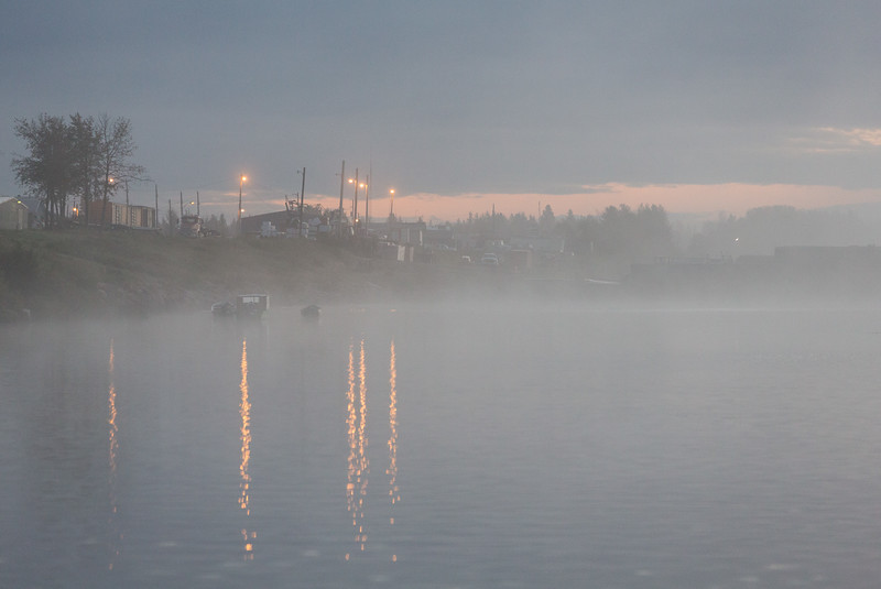 Looking down the Moose River before sunrise through fog towards barge docks.