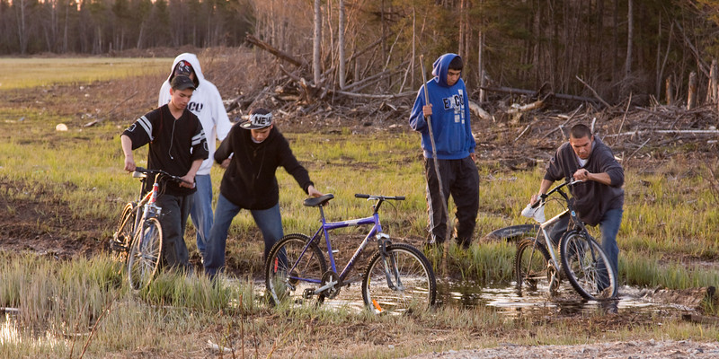 Cyclists make their way through a bit of water in Moosonee.