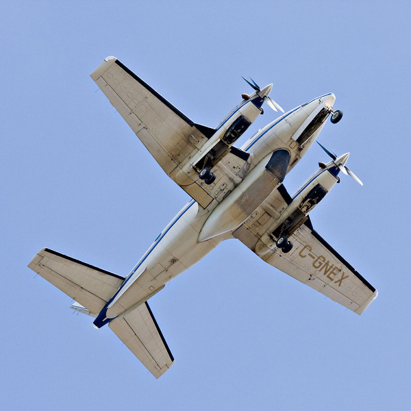 Bottom (overhead) view of Thunder Air Beech A100 King Air C-GNEX over the Moose River shortly after take off from Moosonee.