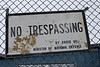 "No trespassing sign at fenced off area behind Moosonee arena, sign is ""antique"" presumably left over from Canadian Forces Station Moosonee which closed in 1975."