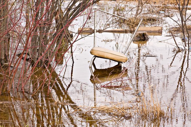 Chair in pond along Bay Road in Moosonee, Ontario
