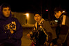 Three friends at night on First Street showing shallow depth of focus meaning that only the person in the center is in focus.