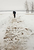 2010 January 25: Anthony Isaac takes advantage of unusually warm weather (2C) to clean off sidewalk at Keewaytinok Native Legal Services in Moosonee, Ontario