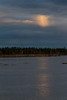 Bright cloud in a dark sky and its reflection on the Moose River.