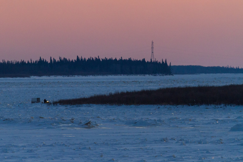 Looking up the Moose River from Moosonee late afternoon around sunset. Snowmobile and sled coming to edge of Bushy Island on way to Moosonee.
