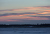 Sky across the Moose River from Moosonee shortly before sunrise. Workers on the ice road.