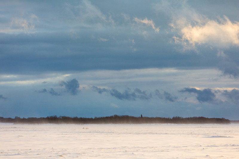 Looking up the Moose River from Moosonee. Blowing snow and fast clouds. Snowmobile and sled headed to Moose Factory.