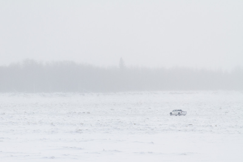 Truck heading across the Moose River from Moosonee to Moose Factory. Blowing snow.