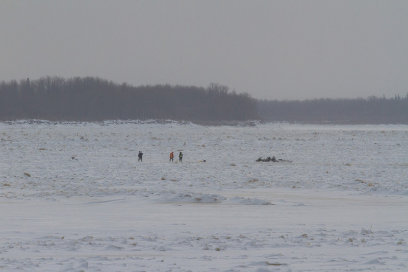 People and snow machines on the Moose River.