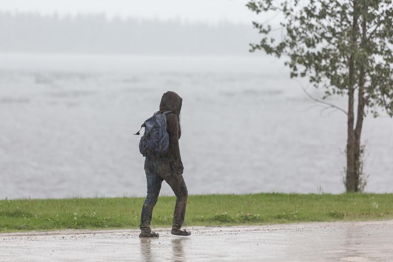 Pedestrian in the rain on Revillon Road in Moosonee.