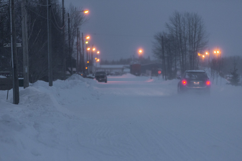 Car on Revillon Road in light blowing snow.