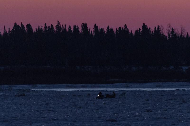 Snowmobile across the Moose River from Moosonee before dawn.