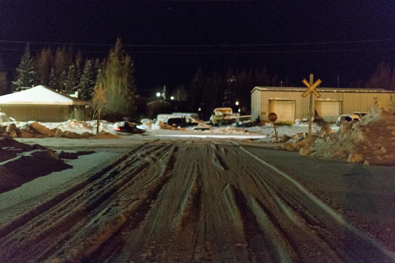Blurry snowmobile on Ferguson Road at night.