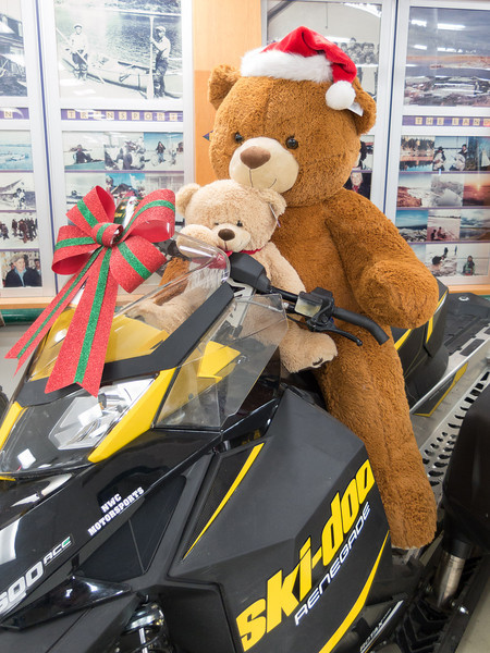 Snowmobile display at Northern Store in Moosonee with large stuffed animals as riders.