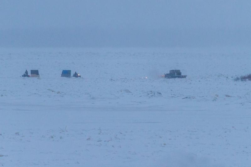 Snowmobiles with sled, snow groomer near Bushy Island.