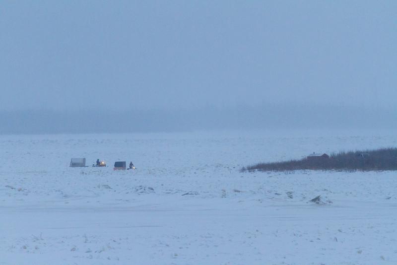 Two snowmobiles and sled approaching Bushy Island near Moosonee.
