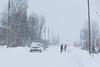 People shoveling snow on Revillon Road in Moosonee.
