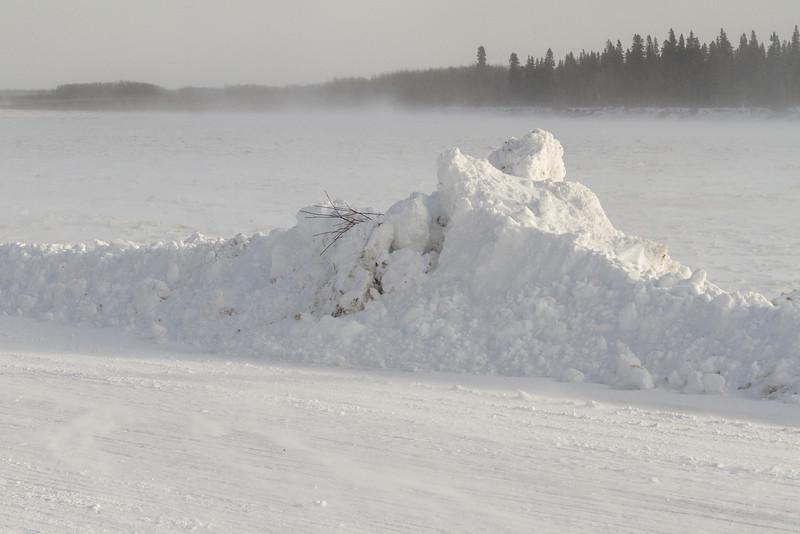 Snow blowing on the Moose River at Moosonee. Snowbank along Revillon Road.