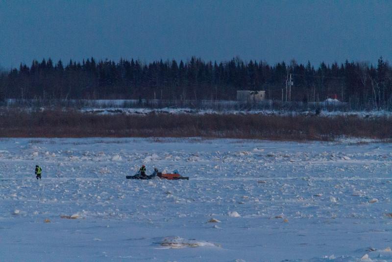 Activity out on the ice. People and snowmachines, Moose Factory in the distance.