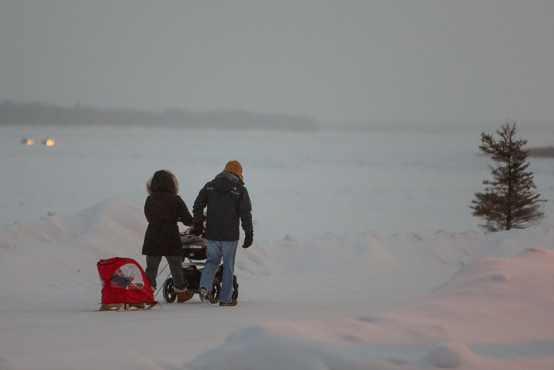 People walking on Revillon Road in Moosonee. Two people with baby carriage and sled.  Traffic on the winter road in the distance.