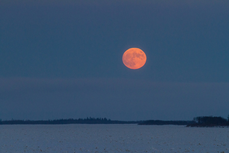 Full moon in the sky over the Moose River around sunset.