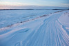 Access road to public docks in Moosonee with snowmobile tracks heading across the river.