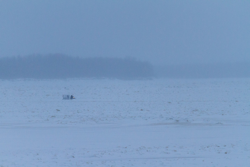 Snowmobile and sled coming across the Moose River to Moosonee.