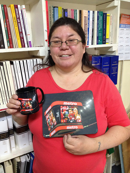 Pauline Sackaney with mug and mouse pad showing picture of her and grandchild at Ottawa hockey arena. 2013 December 18.