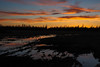 Post sunrise skies reflected boggy ground on other side of tracks in Moosonee. In camera HDR jpg.