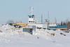 Boats in winter storage along the Moose River in Moosonee. Barge Niska I behind trailer.