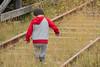 Little boy carrying rocks along the tracks.