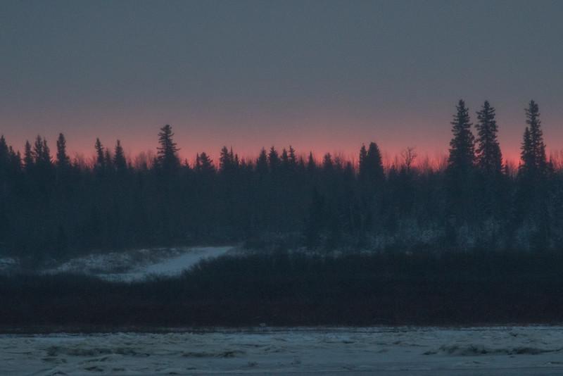 Hints of purple in the sky before sunrise looking across the Moose River from Moosonee.