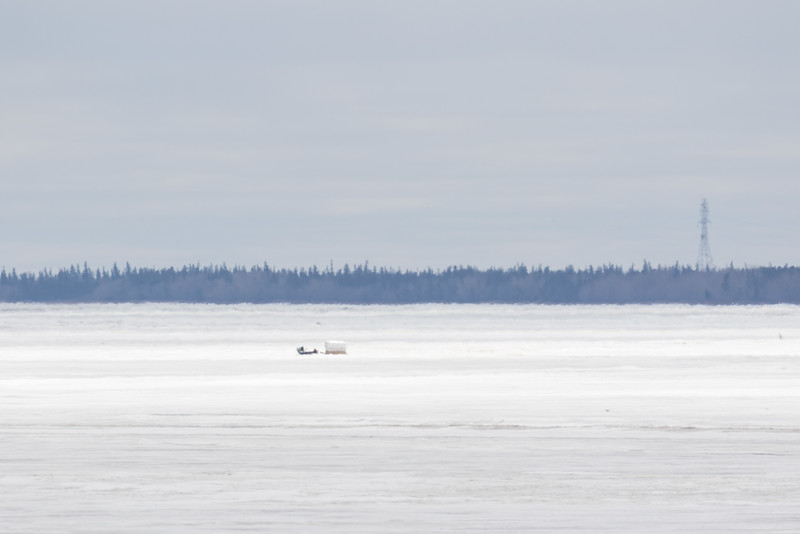 Looking up the Moose River. Snowmobile and sled in the middle. Distorted by heat waves.