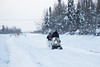 Snowmobile and sled head up the winter road.