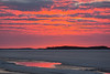 Surface water on the ice of the Moose River reflects the sky before sunrise.