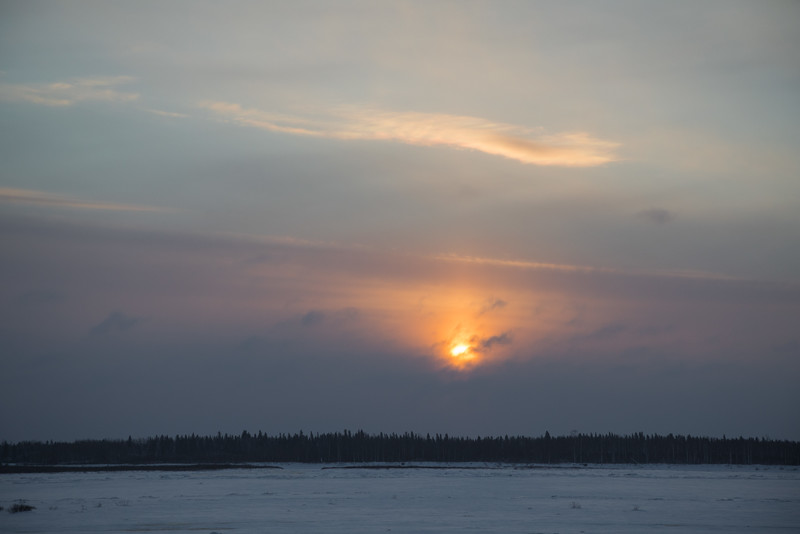 The sun comes up over the clouds across the Moose River from Moosonee 2016 December 30th.