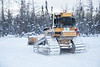 Caterpillar D5M bulldozer clearing snow from the winter road.