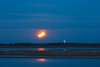 Four minute time exposure of the moon rising across the Moose River from Moosonee with fireworks from Moose Factory Island.