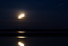 Eight minute time exposure of the moon rising across the Moose River from Moosonee. Streak in upper right is the planet Mars.