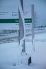 Snow on light pole at Ontario Government building in Toronto has slid down pole in a curve.