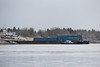 Small tug Harricana River with barges on the Moose River at Moosonee 2016 May 15th. Barge Niska I in winter storage.