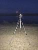 Camera on tripod doing time exposures of the moon rising across the river