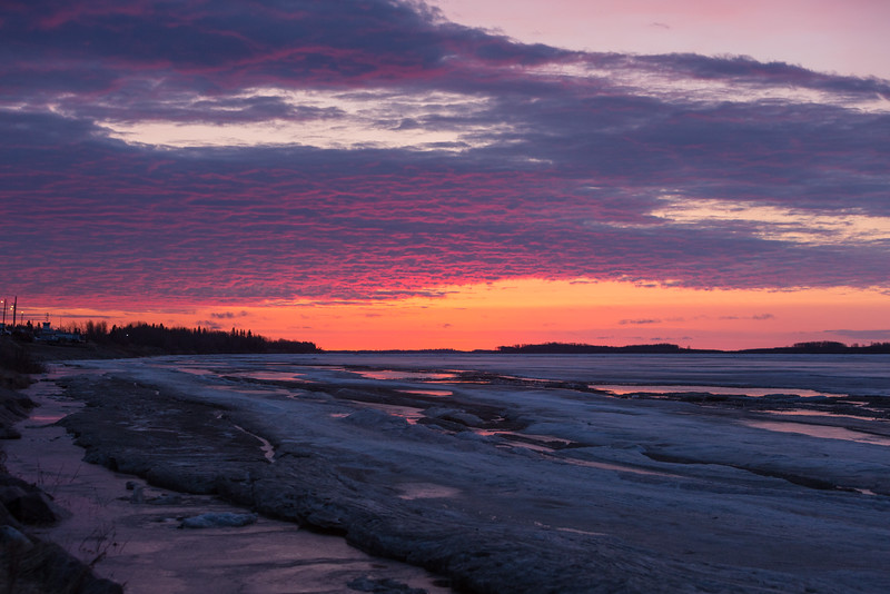 Looking down the Moose River before sunrise. Clouds turn purple above clear sky along horizon. Water on the ice reflects sky.