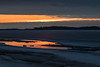 View down the Moose River. Bright streak of sky reflected in water on top of the ice of the Moose River.
